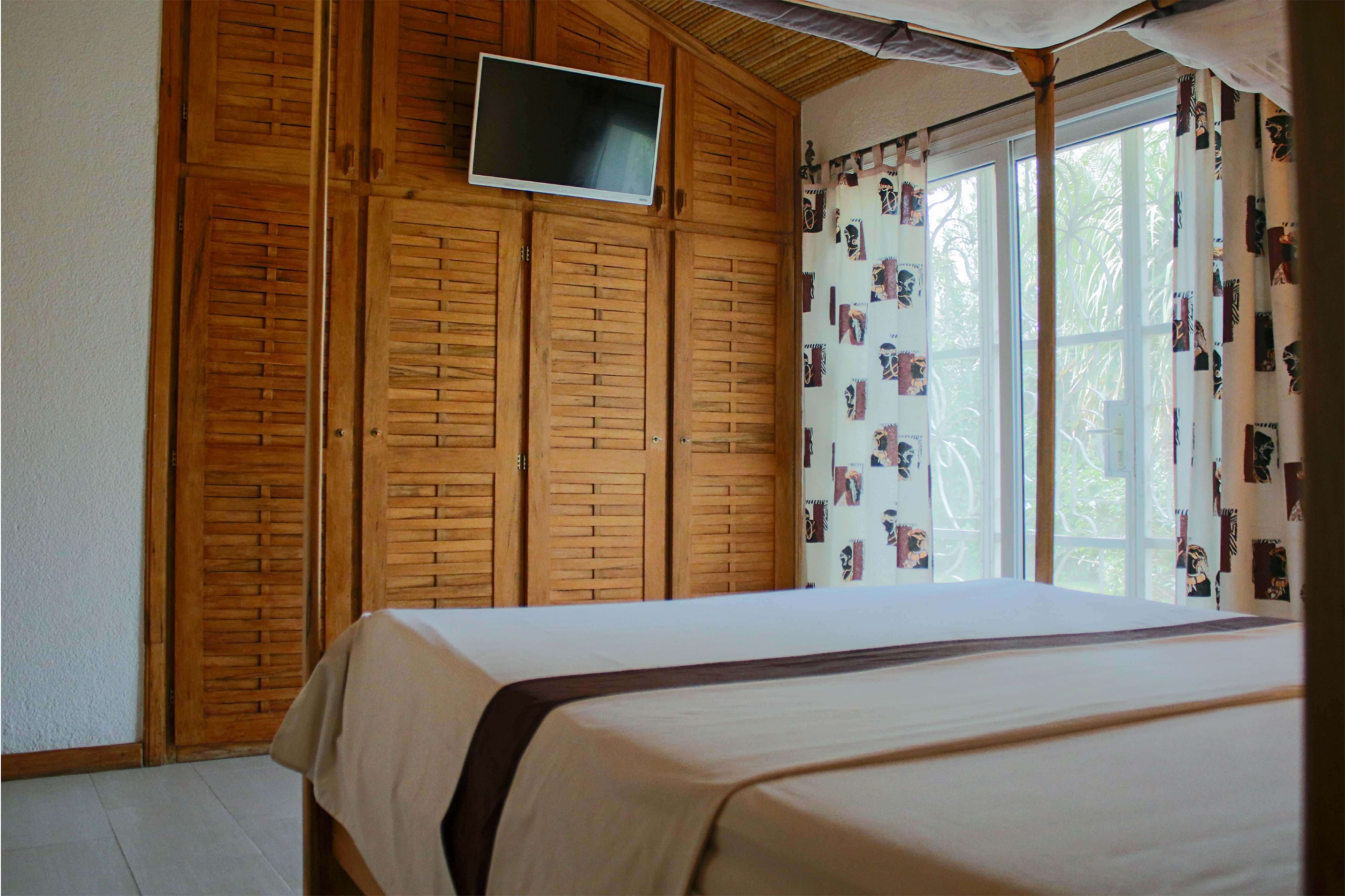 chambre bien équipée avec un lit de 2 places et un accès au jardin
